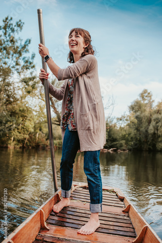 Stampa su Tela A beautiful young woman punts on a boat in a river in Oxford