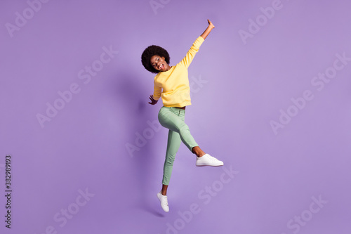 Full body photo of excited dark skin girl jump scream wear yellow green pullover isolated over purple color background