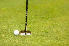 Golf Ball Close To Going Into The Hole Cup With The Flag Still In Close Up Selective Focus