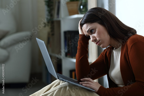 Sad woman checking bad news on laptop in the night