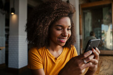 Beautiful Smiling Ethnic Teenage Customer Female Receiving Text From Boyfriend On Smartphone In Trendy Cafe