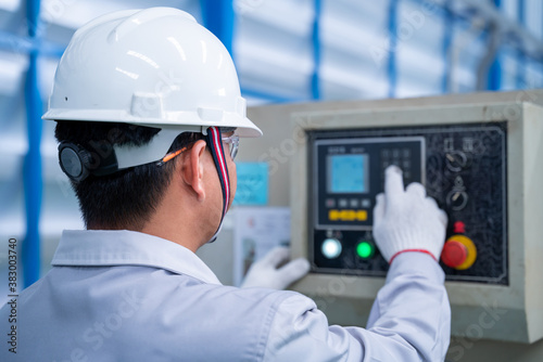 Asian technician worker wearing a safety suit and setting Shearing Machine in industrial factory, Safety first concept.