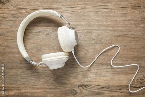Fototapeta White headphones on old wooden table