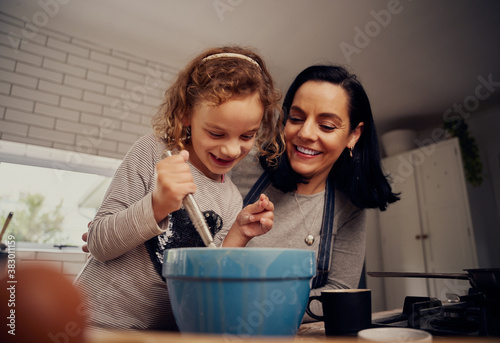 Cuadros en Lienzo Happy mother and daughter preparing batter and dough while mixing with a whisk i