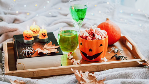 Photo Book, halloween decor, candles, popcorn and drinks on tray on bed, halloween reading concept with bokeh background