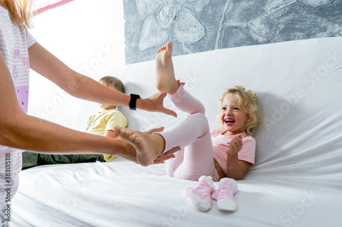 Mom tickles her little daughter's feet. The girl laughs merrily. Canvas-taulu