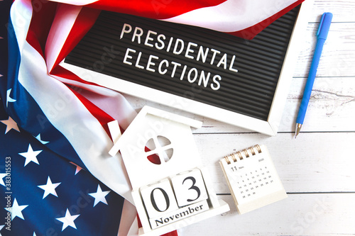 Fototapeta november 3 2020, 59th presidential election in USA. Flat lay composition : United states flag and calendar on white wood background . Vote by Mail Ballot envelopes for election obraz