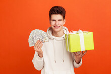 Smiling Satisfied Young Man In Casual Hoodie Holding Gift Box And Bunch Of Money, Holiday Shopping With Cashback, Bank Loan. Indoor Studio Shot Isolated On Orange Background