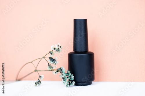 Fototapeta Single bottle of black nail polish gel with sprig of flowers