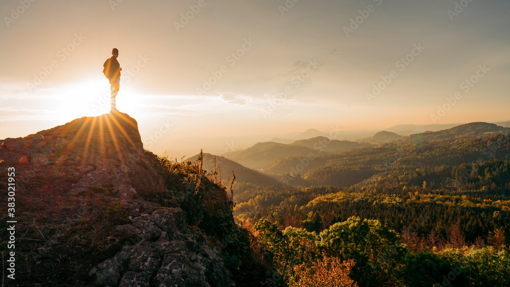 Fototapeta Silhouette of young man on top of rock, sky and sun light background. Adventure, Art, Travel, Hike, Outdoors, Sport, Business, success, leadership, achievement and people concept
