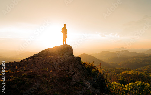 Fototapeta Silhouette man hiker on top of a rocky mountain cliff overlooking the beautiful Czech Nature Landscape during a colorful sunny sunset. Adventure dreamscape composite. Background from national park obraz