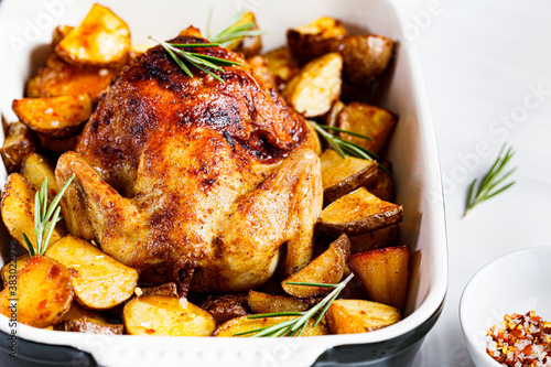 Obraz na plátně Baked whole chicken with potatoes and rosemary in black dish, white background