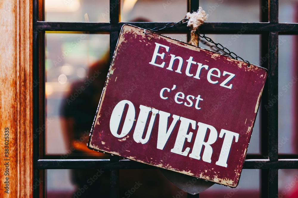 Fototapeta Plaque en métal vintage avec texte Entrez c'est ouvert en français sur la porte d'une boutique