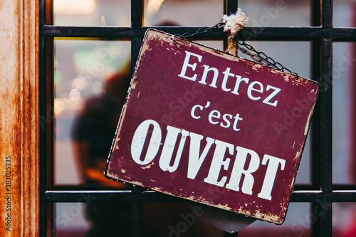 Fotografiet Plaque en métal vintage avec texte Entrez c'est ouvert en français sur la porte