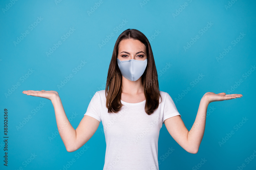 Fototapeta Photo of pretty lady good mood hold open palms arms showing select pick novelty covid infection stop products wear medical mask casual white t-shirt isolated blue color background