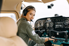 Woman Pilot Sitting In Private Airplane Cockpit, Wearing Headset, Looking At Camera, Smiling.