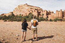 Couple Of Backpacker Travelers On Background Ait Ben Haddou Ksar In Ouarzazate. Welcome To Morocco. Travel Concept. Popular Landmark.