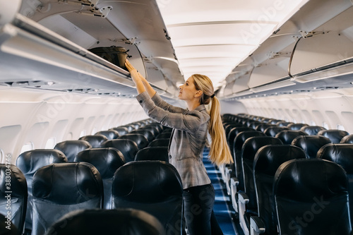 Tableau sur Toile Young woman taking hand luggage out of airplane shelf.