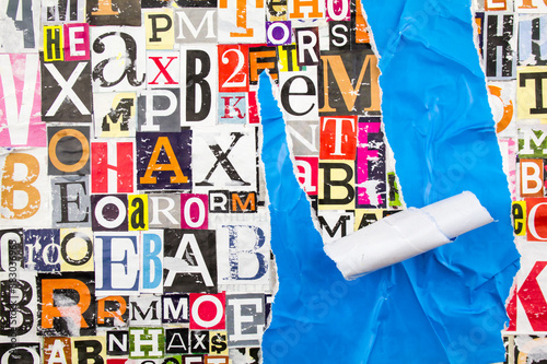 Colorful collage from clippings with letters and numbers and torn crumpled piece of blue paper Fototapet