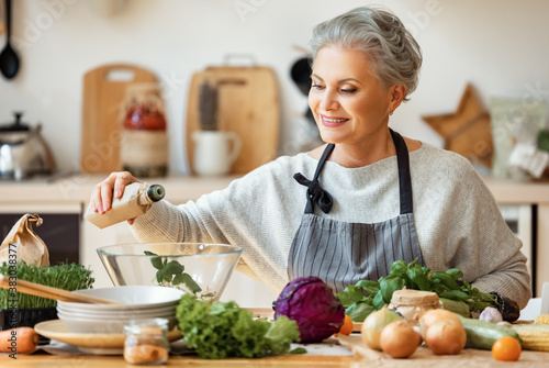 Cheerful middle aged housewife in apron pours vegetable oil into a fresh salad and looking at camera while preparing healthy dish  in home kitchen
