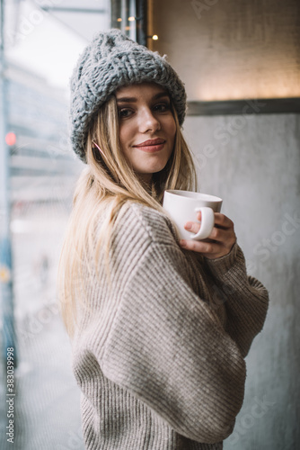 Obraz Half length portrait of trendy dressed customer posing near cafeteria window enjoying coffee time, carefree female in knitted pullover and winter hat holding aroma caffeine beverage for warming - fototapety do salonu