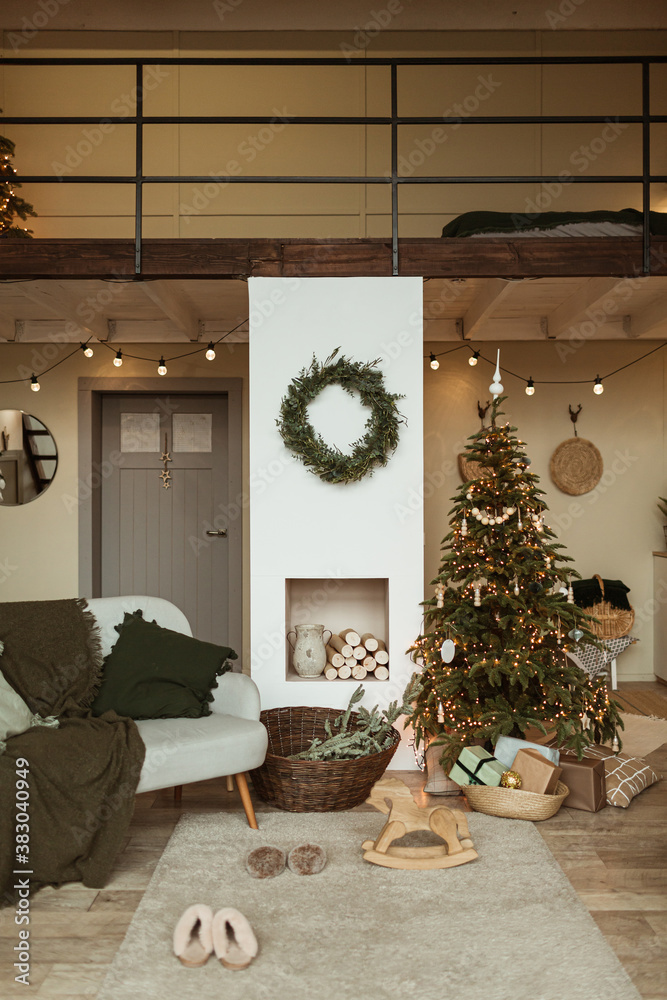 Fototapeta Modern interior design concept. Comfortable cozy living room decorated with Christmas tree with gifts, wreath frame, fireplace, sofa, carpet. Christmas / New Year celebration decorations.