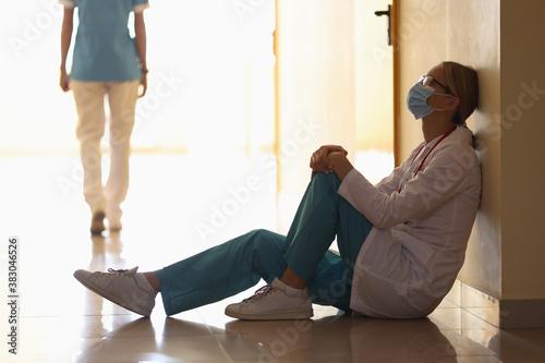 Fotografie, Obraz Doctor in medical mask sits on floor in hospital corridor and walking nurse in background