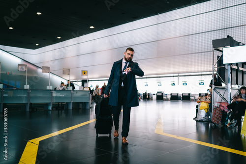 Fototapeta Caucasian businessman checking time on modern smartwatch hurry up to airport gate in terminal, formally dressed commuter with luggage suitcase using wearable wrist clock during work travelling obraz