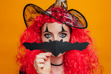Clown Girl In Halloween Costume Covers Her Face With Paper Bat Isolated On Orange Background In Studio