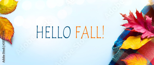 Hello fall message with Autumn leaves and Warm scarf on a blue background