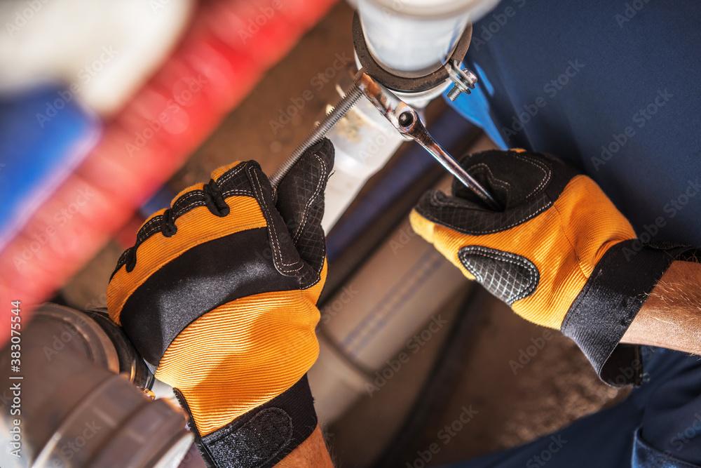 Fototapeta Plumber Worker Adjusting Water and Sewage System Elements
