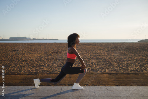 Fototapeta Young sporty black woman on fitness and running workout at city beach. Healthy lifestyle and exercising. Fit athlete stretching for warming up. obraz