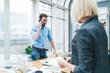Leinwandbild Motiv Man speaking on smartphone standing in workplace