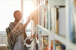 Waist up portrait of young African-American man taking book off shelf in school library against sunlight, copy space