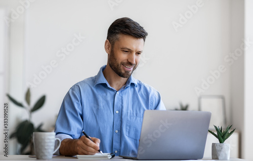 Millennial male entrepreneur using laptop and taking notes at workplace in office
