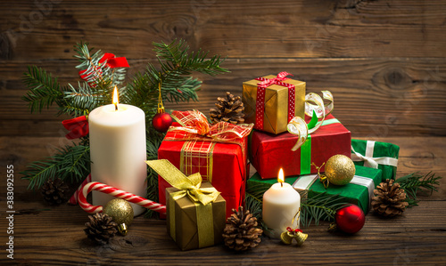 Christmas gifts and candles on the wooden table