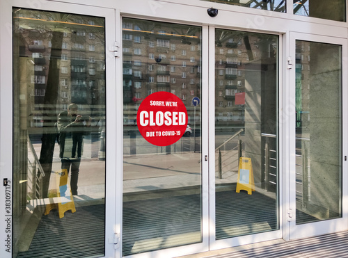 Office building closed due to COVID-19, sign with sorry in street door
