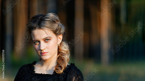 Photo Portrait of a young beautiful woman in a black dress on blurred nature background