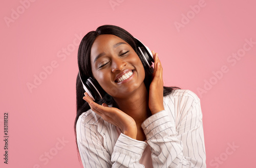 Fototapeta Portrait of pretty African American woman wearing headphones and listening to be