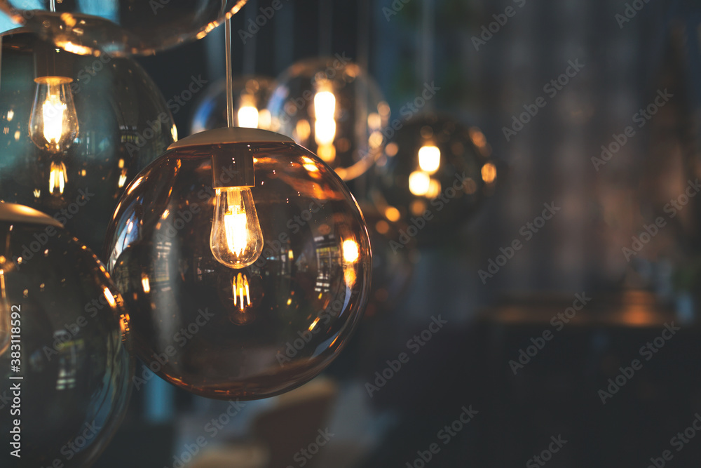 Fototapeta Beautiful and cosy luxury light lamp. Cosy cafe, coffee shop or lounge interior. Vintage and minimal decor. Retro vibes. Many different vintage light bulbs hanging from ceiling, coffee shop interior