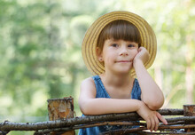 Portrait Of Cute Little Girl In The Forest. Adorable Toddler In A Hat Is Leaning On A Wooden Fence