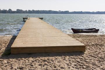 drewniany pomost i łódka nad jeziorem