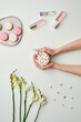 Minimal background composition of female hands holding cup of sweet cocoa over while table background with floral decor and pink accents, copy space