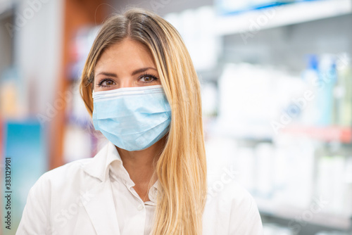 Smiling pharmacist wearing covid coronavirus mask in her pharmacy