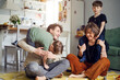 Modern caucasian happy family have fun and speding time with sons at home, parents playing with kids
