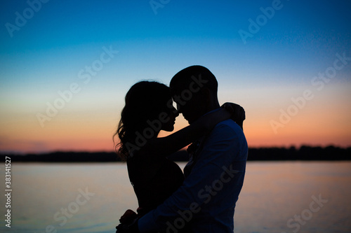 Silhouettes of a couple in love romance at sunset Fotobehang