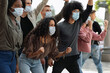 Young people in face masks attending demonstration on the street