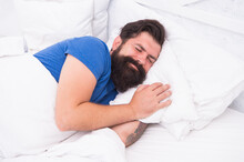 Pleased Caucasian Brutal Man With Mustache Smiling In Bed At Bright Room, Healthy Lifestyle