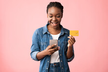 African American Woman Using Smartphone And Credit Card, Pink Background