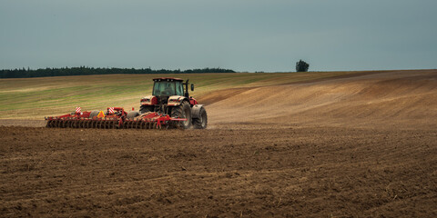 agricultural industrial landscape. a modern tractor with a trailed cultivator works on a hilly field before the autumn sowing campaign